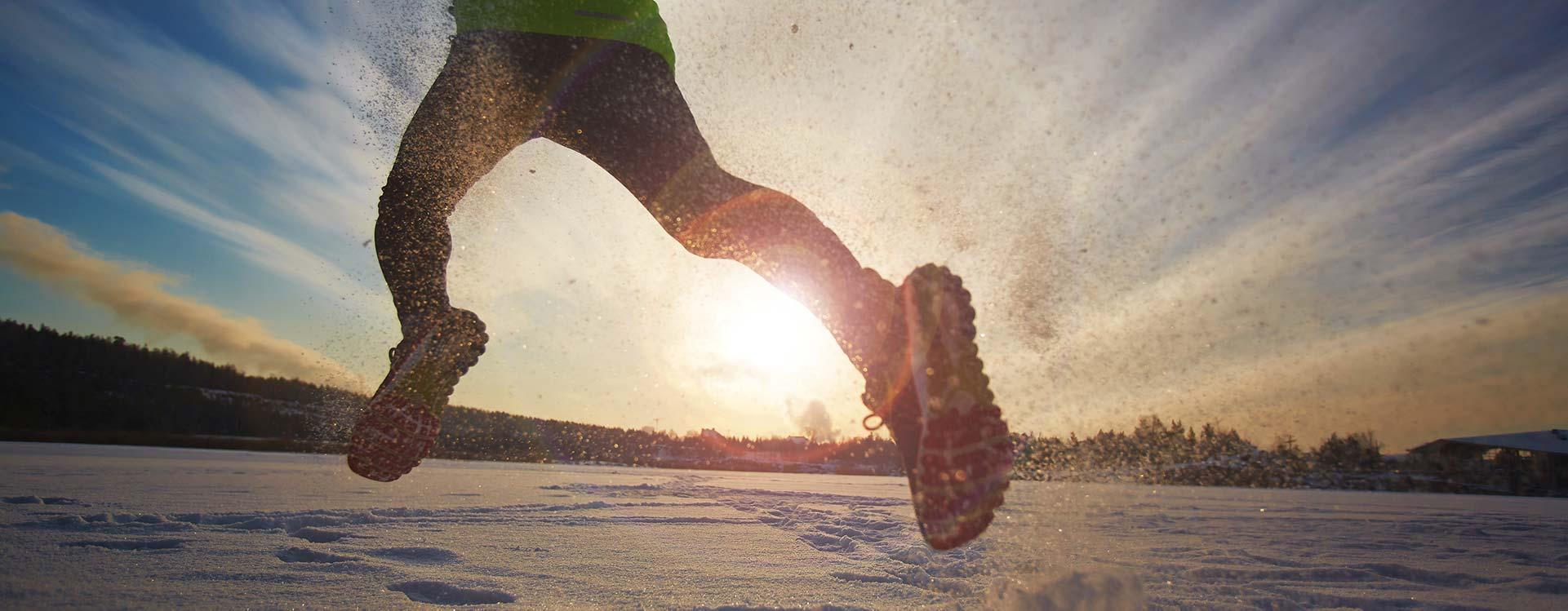 un uomo che corre sulla neve indicata la costanza nell'allenamento e perseveranza nell'attività